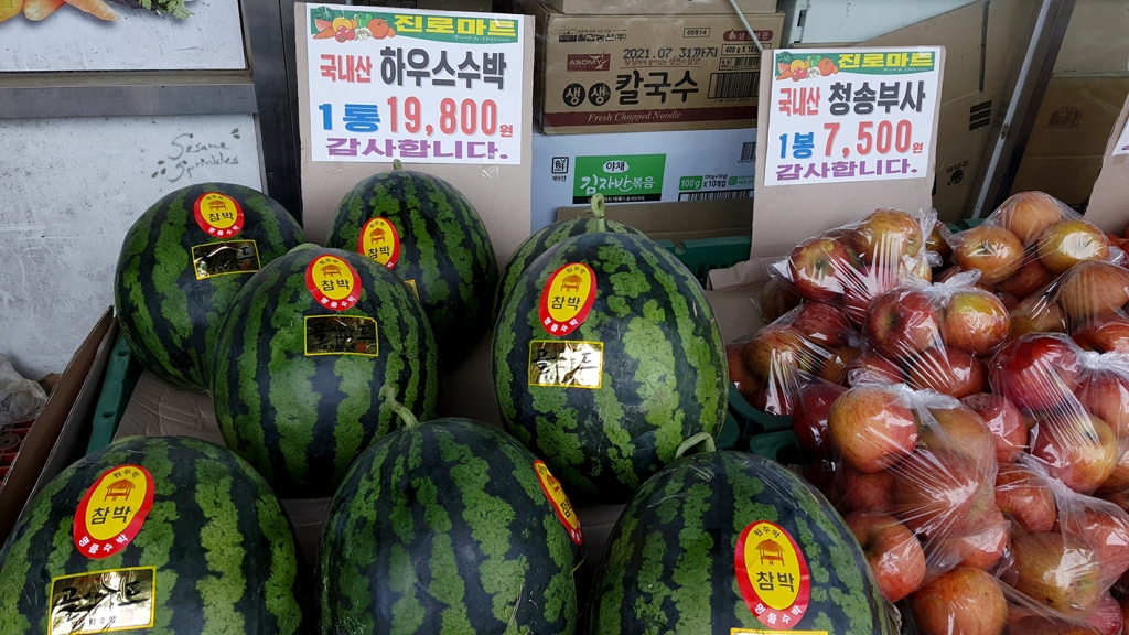 """Storefront with melons and apples. The price tags read """"Greenhouse-grown watermelons"""" and """"Fuji apples from Cheongsong""""."""""""
