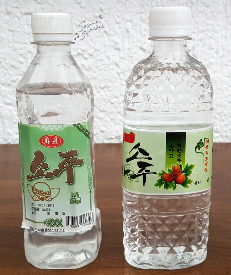 """Clear liquor in clear bottles with green labels. The labels on the two bottles are decorated with images of acorns and say """"Soju"""" in font that it typical for North Korea."""